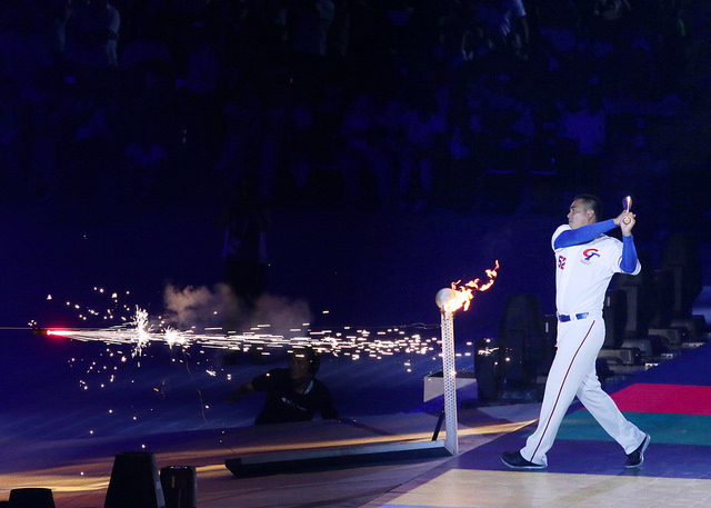 Former Taiwanese professional baseball player Chen Chin-feng sets the Universiade torch alight.