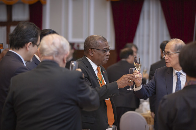 Guests attending a state banquet for St. Christopher and Nevis Prime Minister Timothy Harris toast each other.