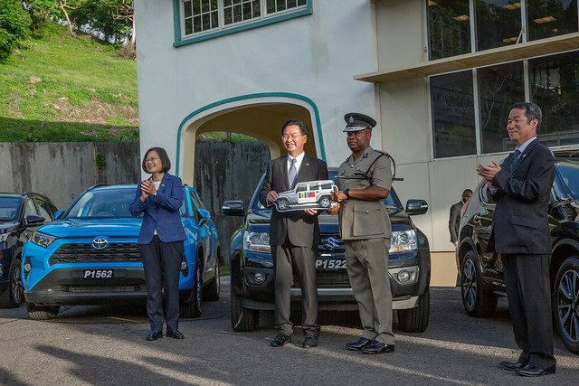 Taiwan's Minister of Foreign Affairs Joseph Wu presents prototype versions of the vehicles to SVG Commissioner of Police Colin John.