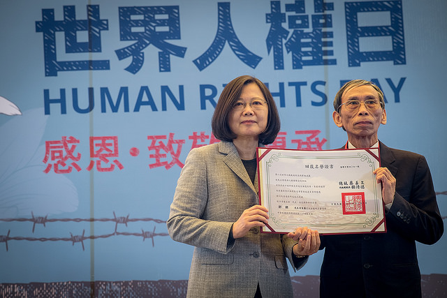 "President Tsai confers a ""certificate of restored reputation"" to Mr. Kuo Chao, which his family member accepts on his behalf."