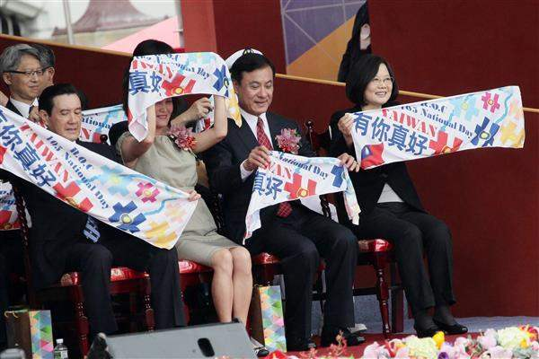 President Tsai holds up a banner during the National Day celebration to greet performing troupes.