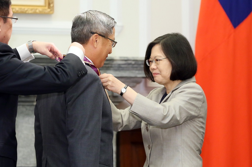 The President is assisted by the Director-General of the Office of the President's Third Bureau to decorate the recipient with a medal.